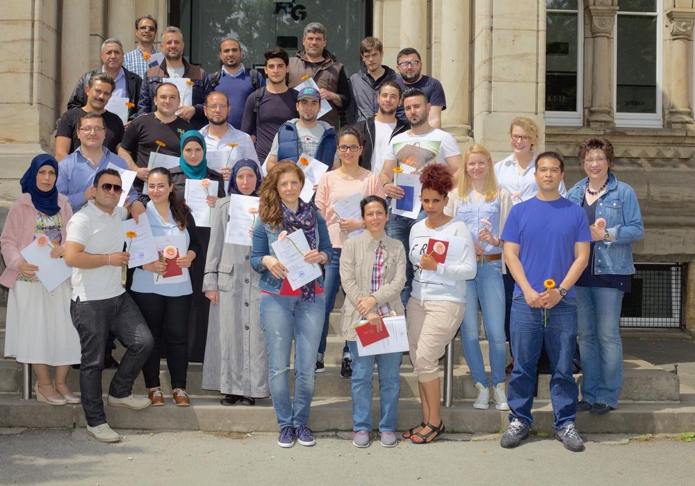 Vorn, von rechts: Dorothe Prozell, Kai Zwarer, Juliane Mahnkopf und Tabea Hillger, zusammen mit den 23 erfolgreichen Deutschkurs-Teilnehmern. Foto: Alec Pein