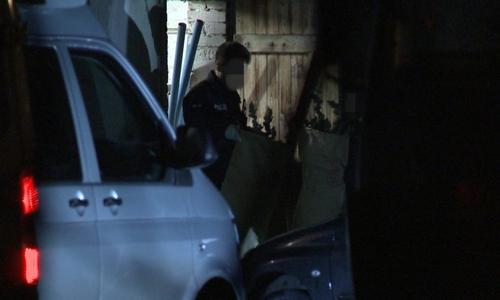 Beamte tragen säckeweise Drogen aus dem abgeschiedenen Haus.