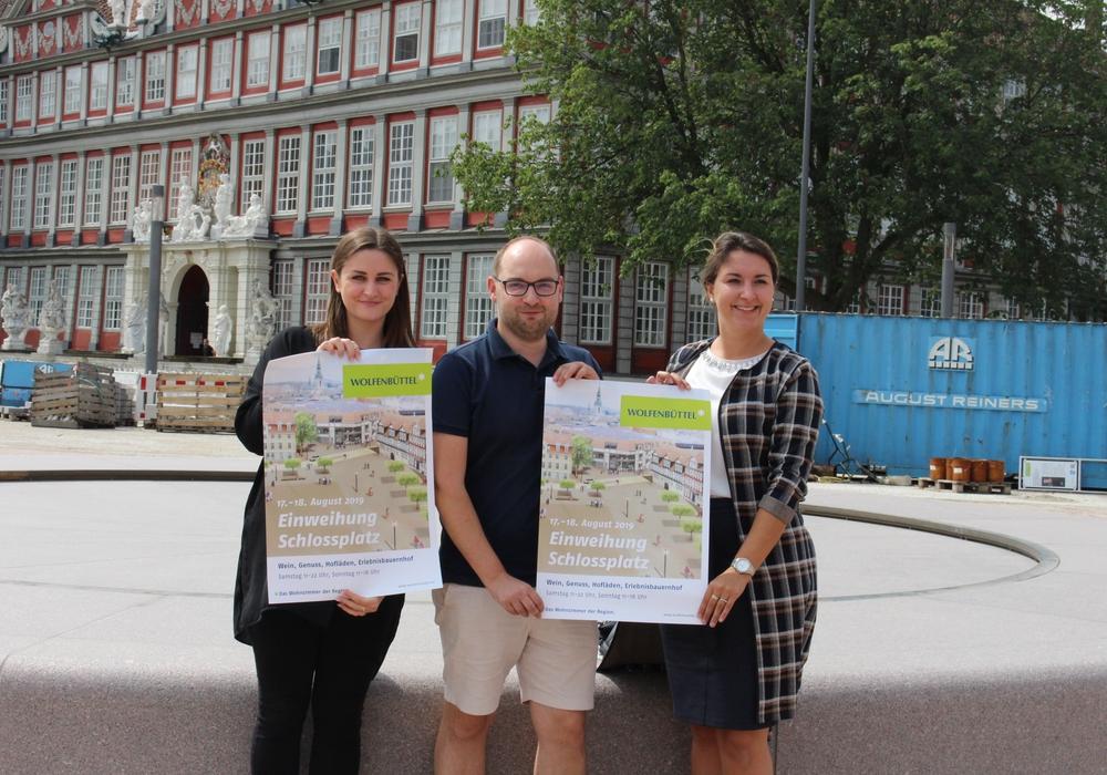 Vivien Strümpfler, Sebastian Kirchner und Anna Wohlert-Boortz präsentieren das Plakat zur Schlossplatzeinweihung vor dem neuen Brunnen. Foto: Marvin König