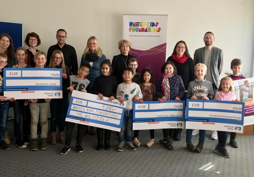 Claudia Kayser, Leiterin der Direktion Wolfsburg (hinten, Mitte), mit den Vertretern der Gewinnerschulen des United Kids Foundations Bambinilaufs. Foto: Volksbank BraWo