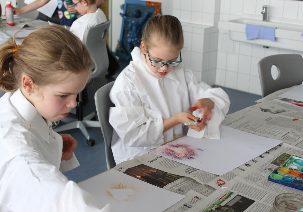 Die beiden Emilys zeigen ihre Kreativität bei der Farbspritztechnik mit einer Zahnbürste. Foto: Max Förster