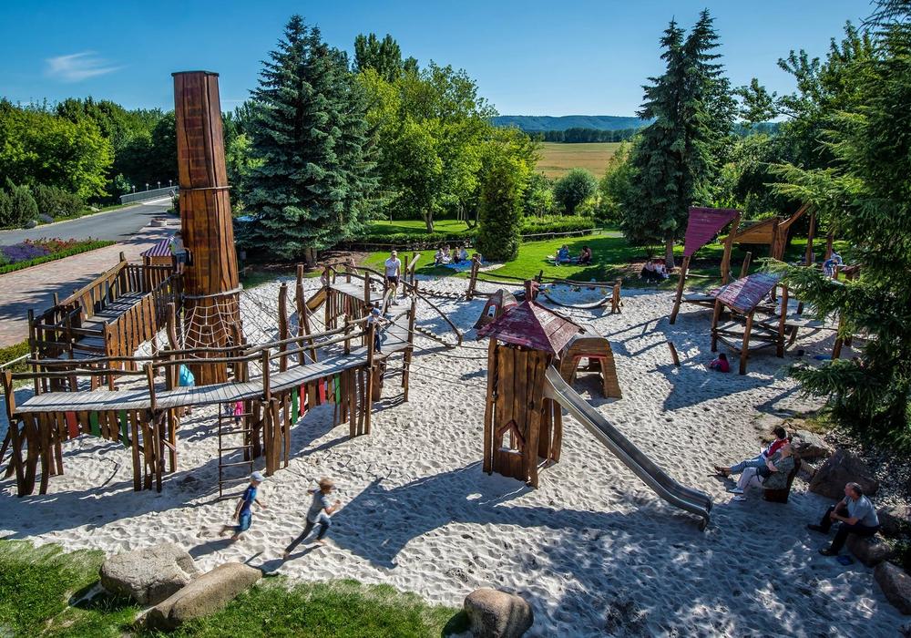 Der Erlebnisspielplatz lockt mit Schaukelbrücken, Holztürmen, Kletterseilen und einem großen Sprunghügel. Foto: Glasmanufaktur Harzkristall