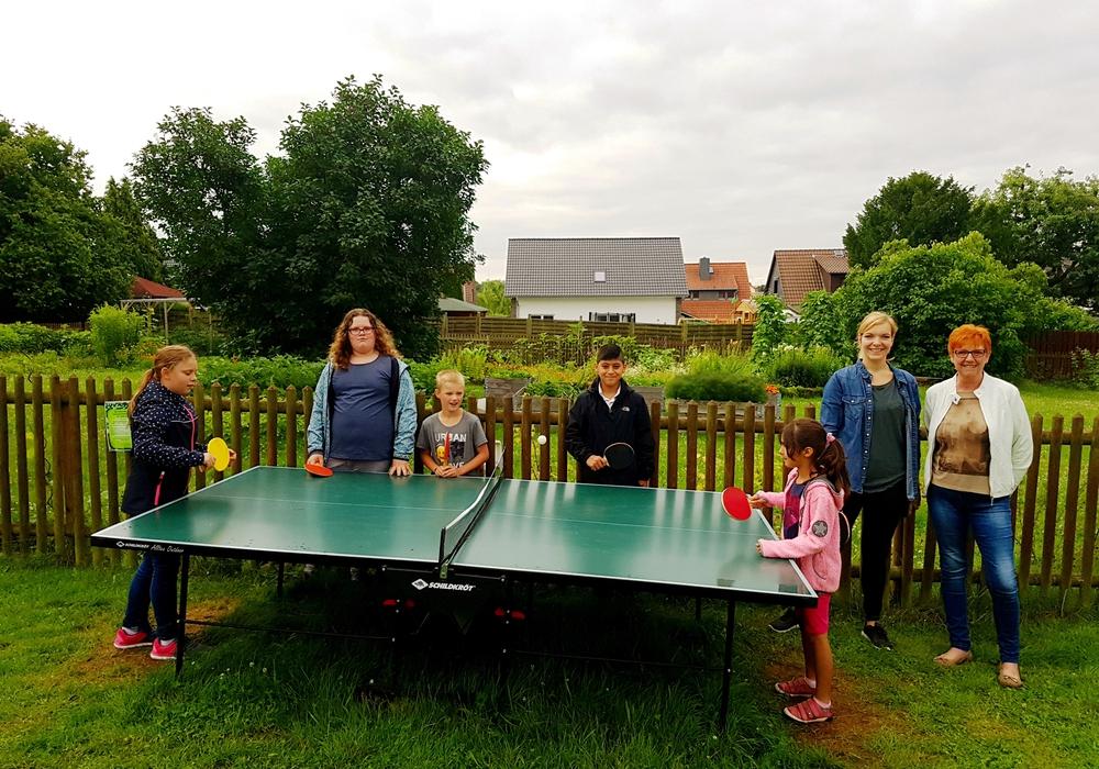 Die Ulmen-Kinder Sarah (von links), Jennifer, Jonas, Orhan, Shina sowie Susanne Pensler und Katrin Lettow freuen sich über die Tischtennisplatte im Gemeinschaftsgarten. Foto: Ulme