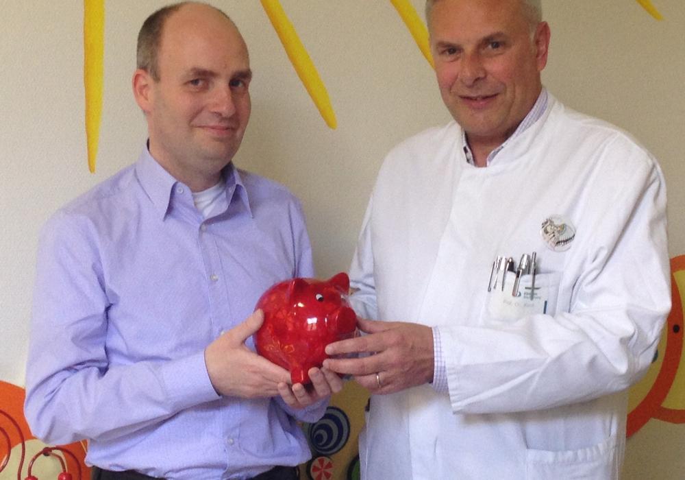 Thomas Kleine-Besten überreicht Prof. Dr. Hans Georg Koch, Chefarzt der Klinik für Kinder- und Jugendmedizin, das rote Sparschwein. Bildnachweis: privat