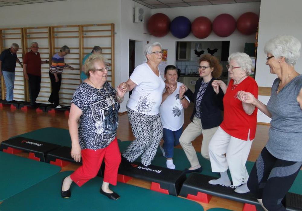 Einen konzentrierten Damenknicks bitte: die Rheuma- Patienten trainieren gemeinsam mit Übungsleiterin Hilde-Anna Strehlow (r.) und Sparkassensprecherin Alexa von der Brelje (3.v.r.) ihren Sinn fürs Gleichgewicht. Foto: Sparkasse Gifhorn-Wolfsburg