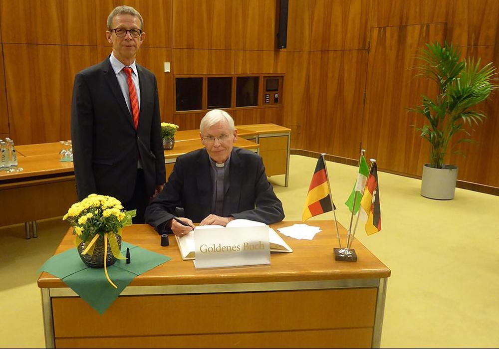 Weihbischof Dr. Nikolaus Schwerdtfeger trägt sich ins Goldene Buch der Stadt Wolfsburg ein. Foto: Stadt Wolfsburg
