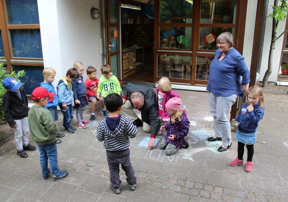 Pastor Friedhelm Siegemund demonstriert den Kindern seine Malkünste. Foto: Christoph Böttcher