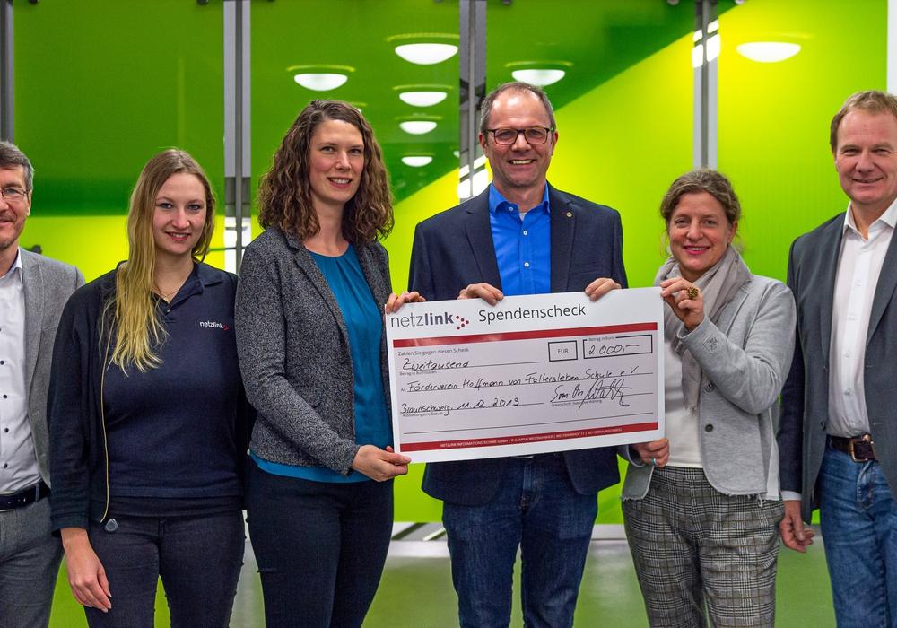 Wiebke Ludwig und Nina Kokemoor von der Netzlink Informationstechnik GmbH übergeben den 2.000 Euro hohen Spendenscheck an den Förderverein der HvF.  Foto: Netzlink Informationstechnik GmbH/HvF