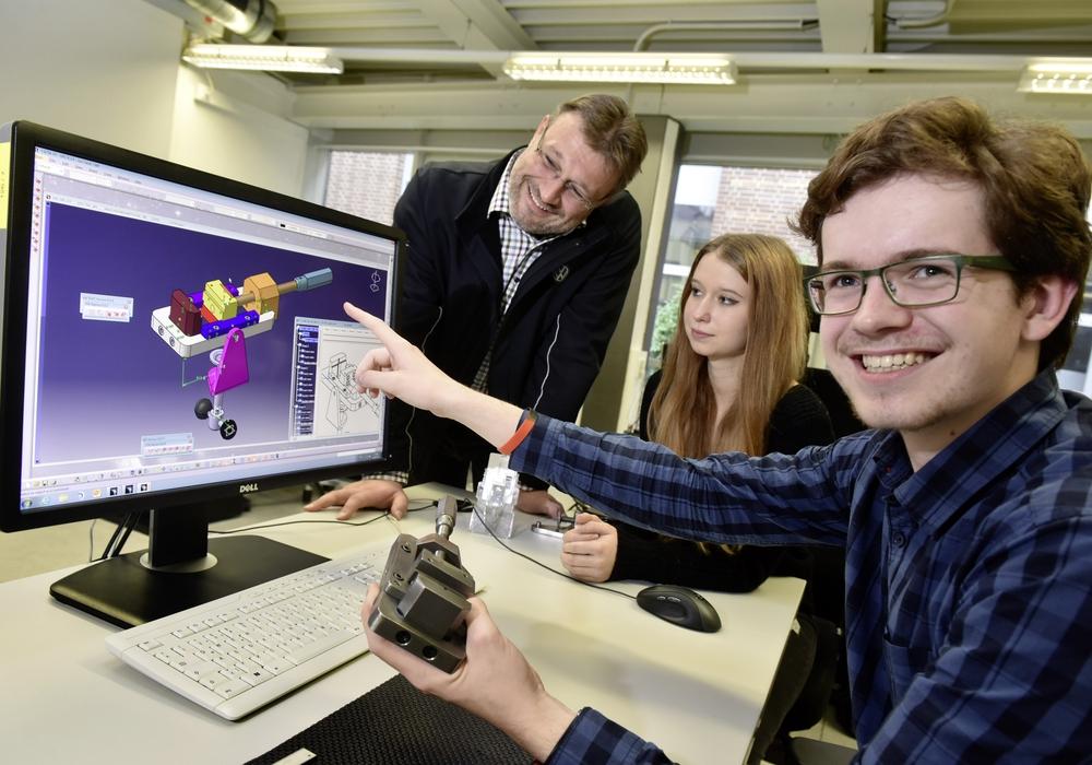Adrien Hebert (17, vorn rechts) erkundet bei Volkswagen die Berufswelt, hier mit Ausbilder Sven Birke (links) und der Auszubildenden Lea Tiebe (18, Mitte) am Beispiel eines mobilen Schraubstocks, wie Technische Produktdesigner Werkstücke am Bildschirm konstruieren. Foto: Volkswagen AG