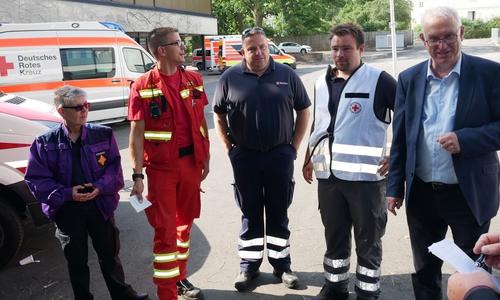Vertreter der Hilfsorganisationen (Notfallseelsorge, DLRG, Malteser, DRK) und Erster Stadtrat Werner Borcherding im Gespräch. Die Stimmung ist gelassen. Bisher verläuft die Evakuierung ohne weitere Vorkommnisse.