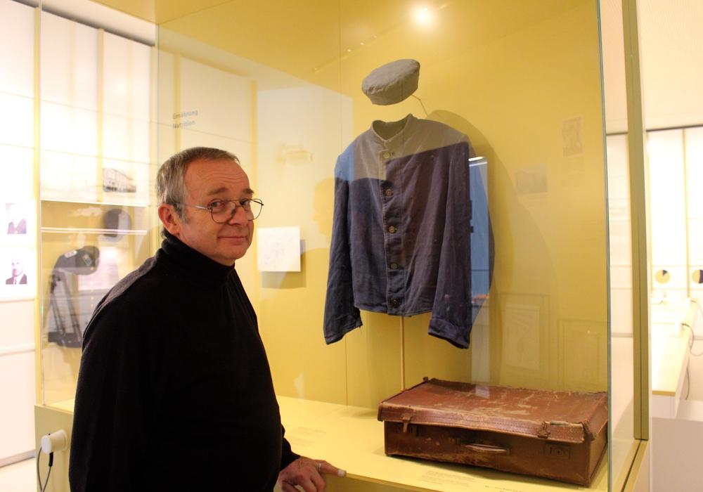 André Charon vor der Häftlingskleidung seines gleichnamigen Vaters. Dieser spielte bei der medizinischen Versorgung der Gefangenen vor der Befreiung des Gefängnisses eine entscheidende Rolle. Fotos: Marvin König