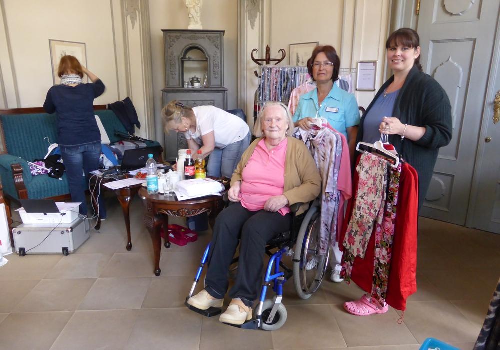 Bewohnerin Elly Dietrich wird von Pflegedienstleitung Bärbel Dietrich und Therapeutin Sabrina Wilke begleitet, und die Mitarbeiterinnen von DEKU-Moden bemühen sich um die passende Auswahl für die Kundin. Foto: Seniorenbetreuung Schloß Schliestedt