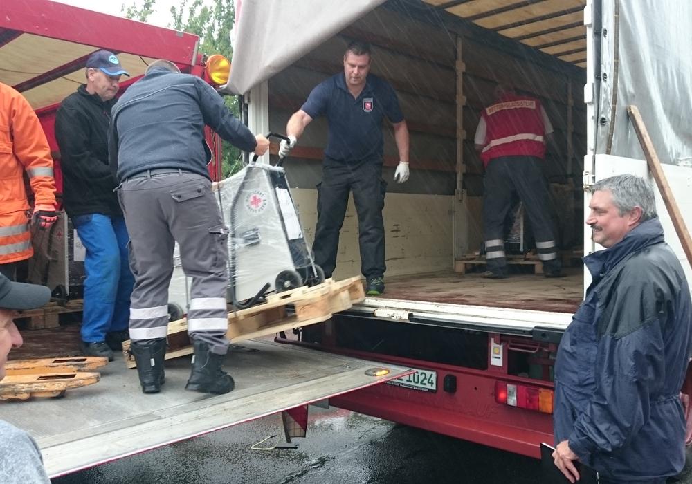 Kräfte von Feuerwehr, DRK und Kommunen beim Aus- und Verladen der Bautrocknungsgeräte. Foto: Volker Junge / Feuerwehr Goslar