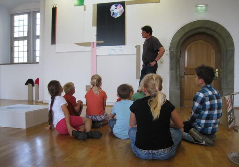 Künstler Kai Schiemenz zeigt den Kindern seine Werke. Foto: Stadt Wolfsburg