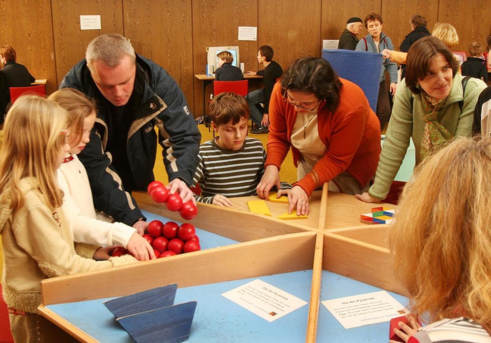 Kinder und ihre Eltern probieren sich am sogenannten Knobeltisch aus. Foto: Veranstalter