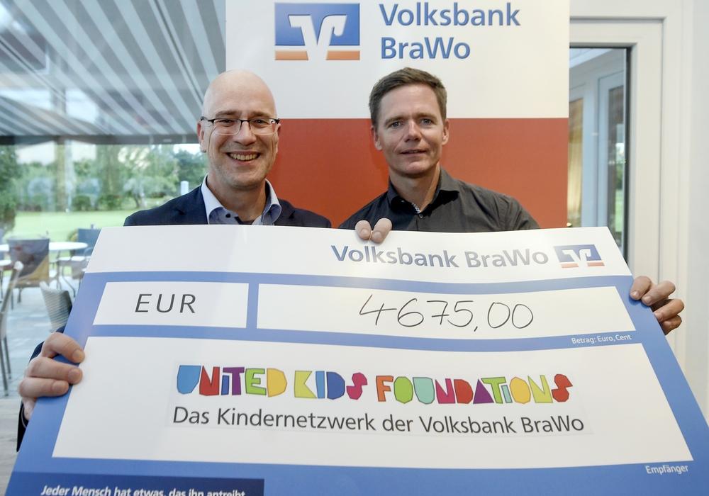 Martin Ihlemann, Sieger der Brutto-Wertung des Golfturniers (rechts), übergibt den Spendenscheck an Stefan Honrath, Botschafter von United Kids Foundations. Foto: Volksbank Braunschweig BraWo