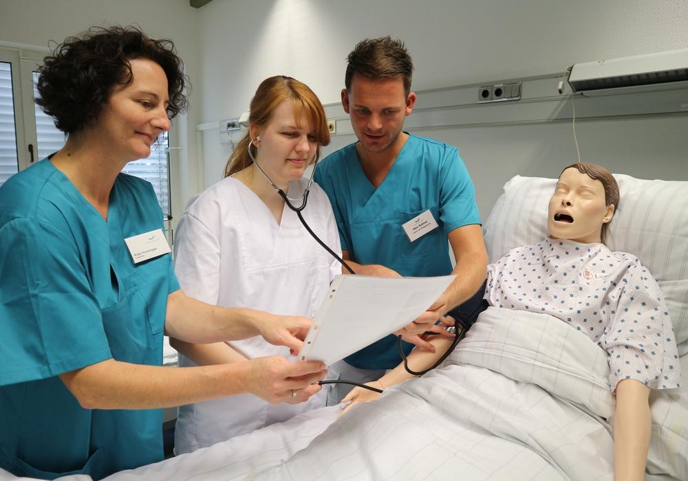 """Die beiden Lehrer Chris Köhne und Katja Hunsrügge erklären der Auszubildenden Jaqueline Wilfling die Blutdruckmessung an der Pflegepuppe """"Nursing Anne""""."""