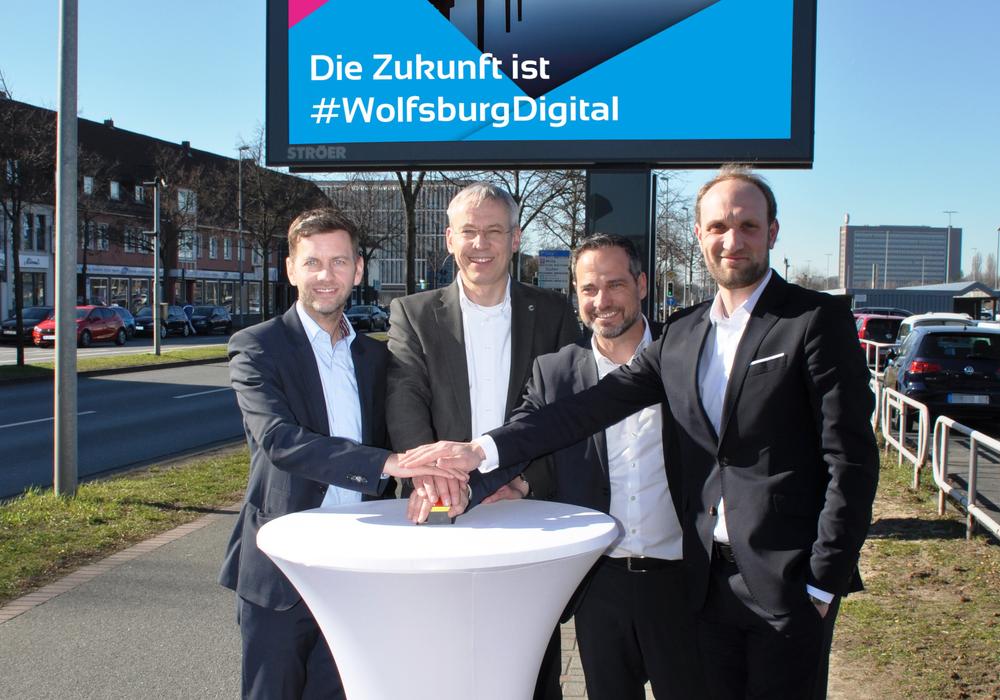 Dennis Weilmann, Kai-Uwe Hirschheide, Dirk Geßner und Jens Hofschröer nahmen die neuen, digitale Informationsflächen gemeinsam in Betrieb (v. li.). Foto: Stadt Wolfsburg