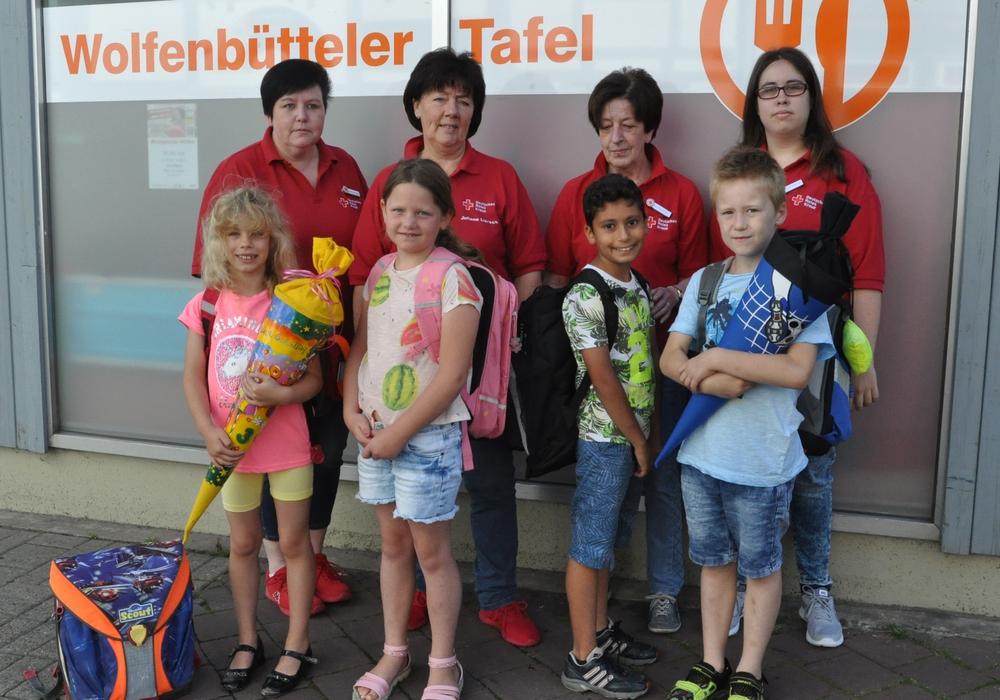 Die Tafelmitarbeiterinnen Susanne Smyczek (hinten von links), Juliane Liersch, Ursula Pflug und Denise Smyczek überreichen den ersten vier Kindern ihre neuen Schulutensilien. Foto: DRK