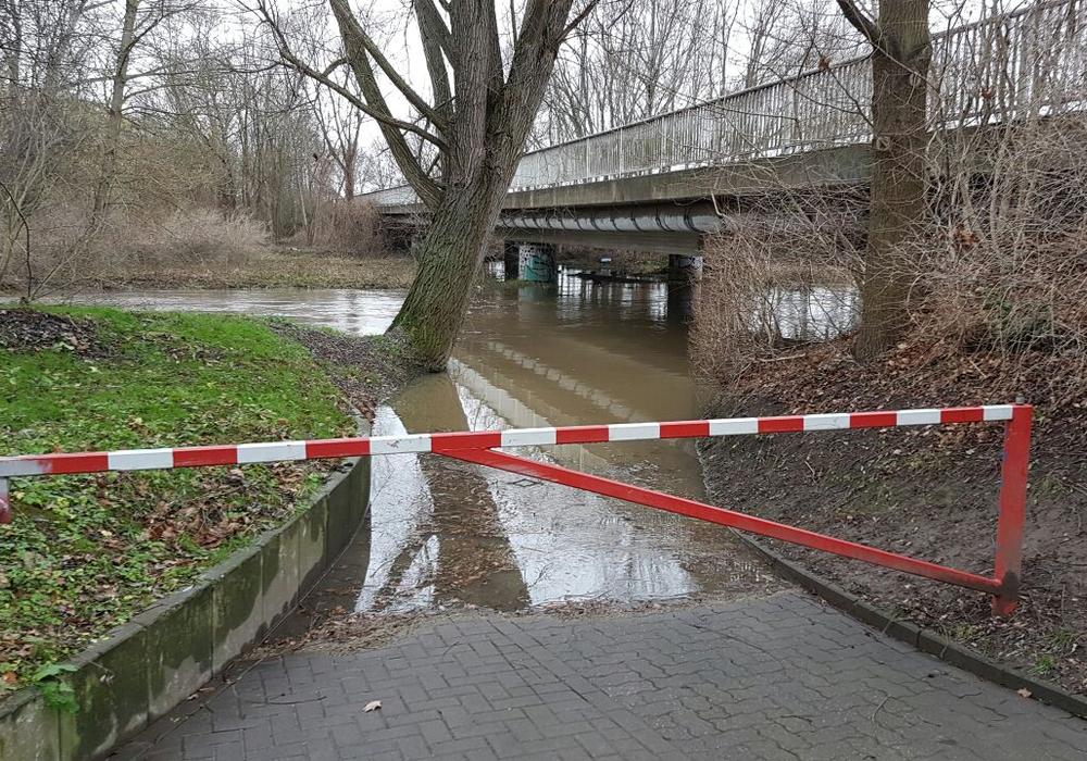 Einige Wege und Flächen entlang der Oker stehen unter Wasser. Hier: Brücke unterhalb der Friedrich-Ebert-Straße mit der Schranke und Blick Richtung Groß Stöckheim. Foto: Feuerwehr Wolfenbüttel