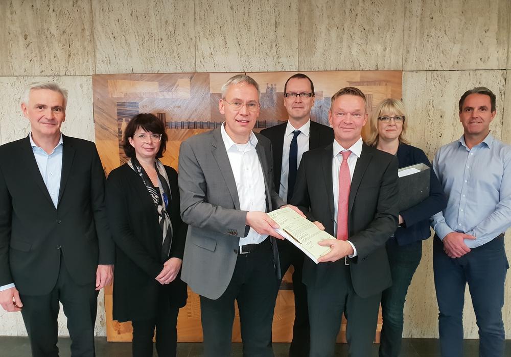 Stadtbaurat Kai-Uwe Hirschheide (dritter von links) übergibt die Baugenehmigung an Marco Meyer (Buhlmann Immobilien, dritter von rechts). Foto: Stadt Wolfsburg.