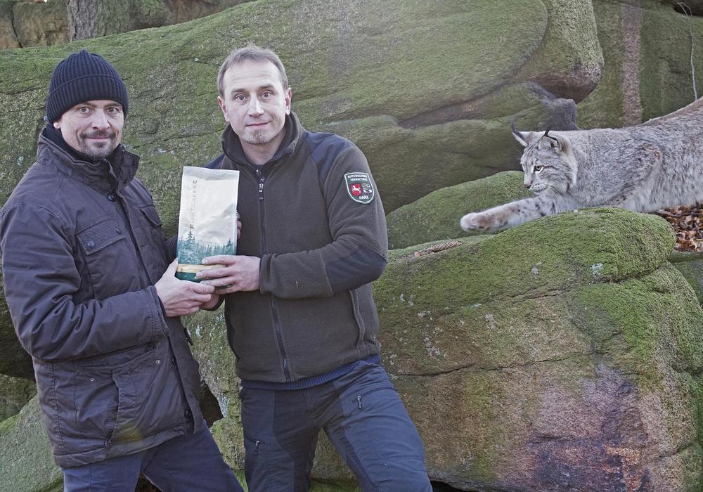 """Ole Anders (rechts) übernimmt das erste offizielle """"Luchs-Kaffeepaket"""" von Mark Schnibbe. Foto: Nationalpark Harz."""