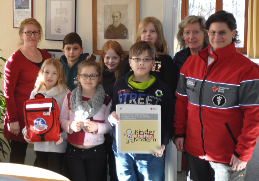 Melanie Niestrop (von rechts) überreichte das Erste-Hilfe-Startpaket an die Mobilitätsbeauftragte Gunhild Gambke sowie die Viertklässler der Wilhelm-Raabe-Schule und deren Schulleiterin Heidi Brackmann. Foto: DRK