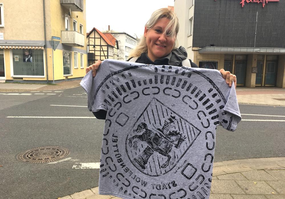 Cathy präsentiert ihr Andenken: Ein bedrucktes T-Shirt mit dem Gully-Deckel-Motiv des Wolfenbütteler Wappens. Fotos: Nick Wenkel