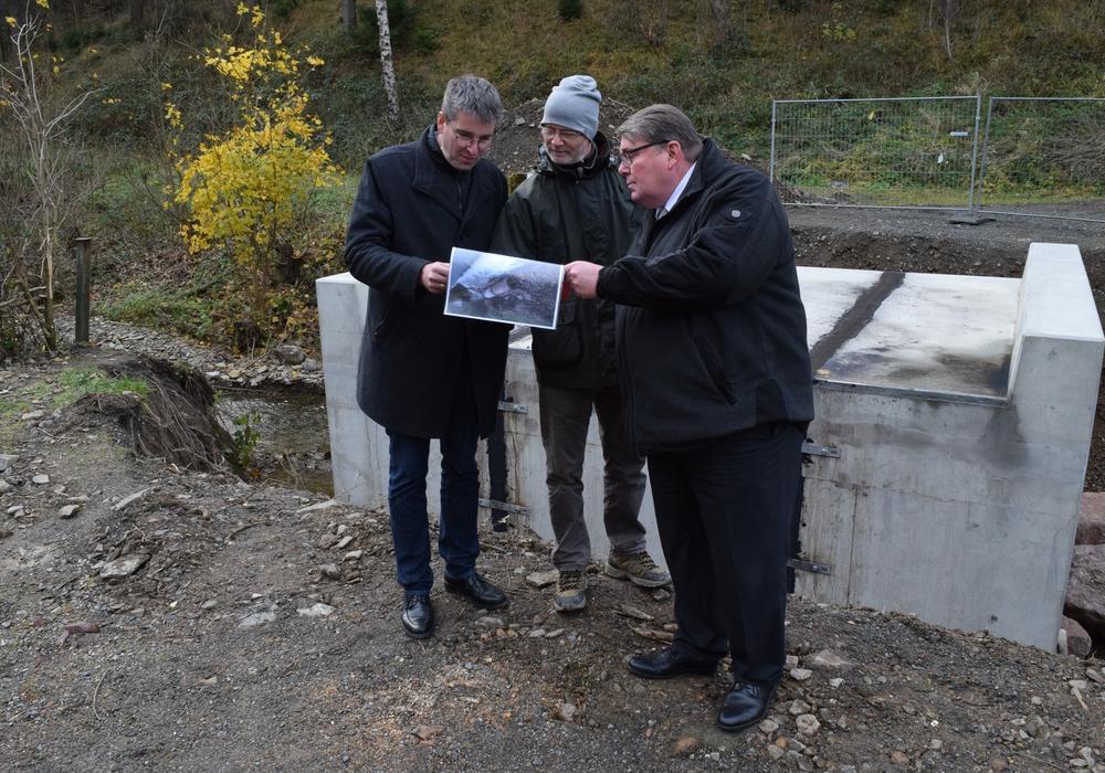 Wolfgang Lebzien (Mitte) zeigt Renke Droste (rechts) und Dr. Oliver Junk vor der neuen Brücke Fotos von den zerstörten Wegen in der Forst. Foto: Stadt Goslar
