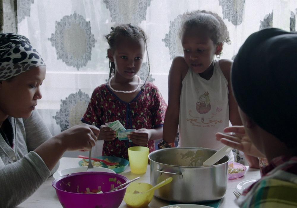 Yasmin sitzt mit Kindern am Esstisch. Foto: MADE IN GERMANY Filmproduktion GmbH