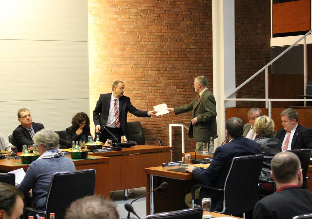 Bürgermeister Klaus Saemann überreicht dem Ratsherrn Bernd Kielhorn (SPD) die Pflichtbelehrung für Ratsleute. Foto: Frederick Becker