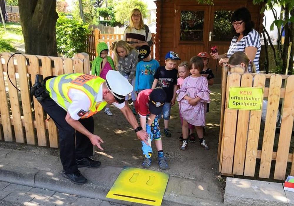 """Polizeikommissar Ralf Buchmeier (Verkehrssicherheitsberater der PI Goslar) sprüht zusammen mit den Kindern die """"Gelben Füße"""". Foto: Polizei Goslar"""
