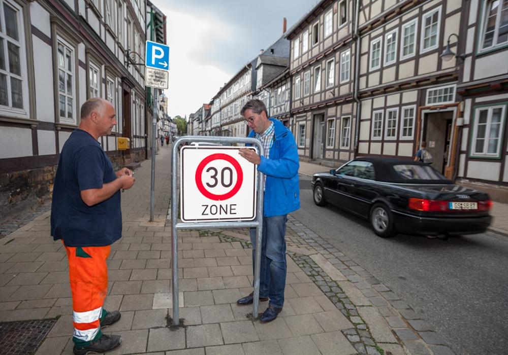 Betriebshof Mitarbeiter Frank Krauter und Oberbürgermeister Dr. Oliver Junk bringen das erste von 17 30-Zonen-Schildern in der unteren Altstadt vor dem Breiten Tor an. Foto: Alec Pein