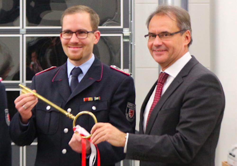 Oberbürgermeister Ulrich Markurth übergibt einen symbolischen Schlüssel an Ortsbrandmeister Dennis Kelpen. Foto: Robert Braumann