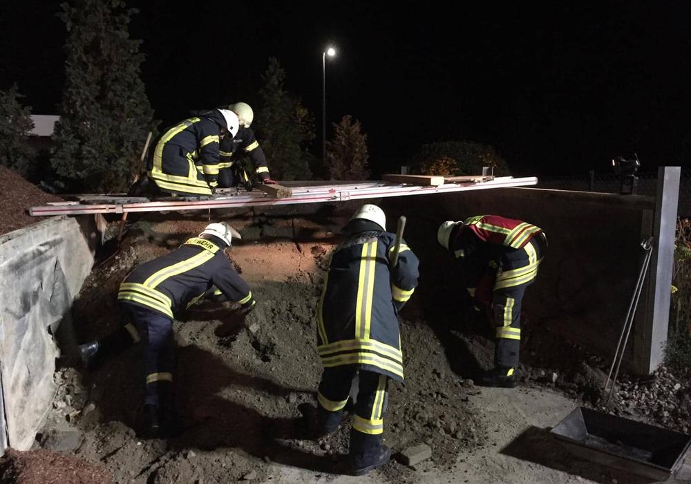 Mehrere Feuerwehrleute während der Rettungsaktion am Kieshaufen. Es galt mit Schaufeln und Lanzen einen aufgeschütteten Haufen Kies zu durchsuchen. Foto: Tobias Stein/Philipp Meyer