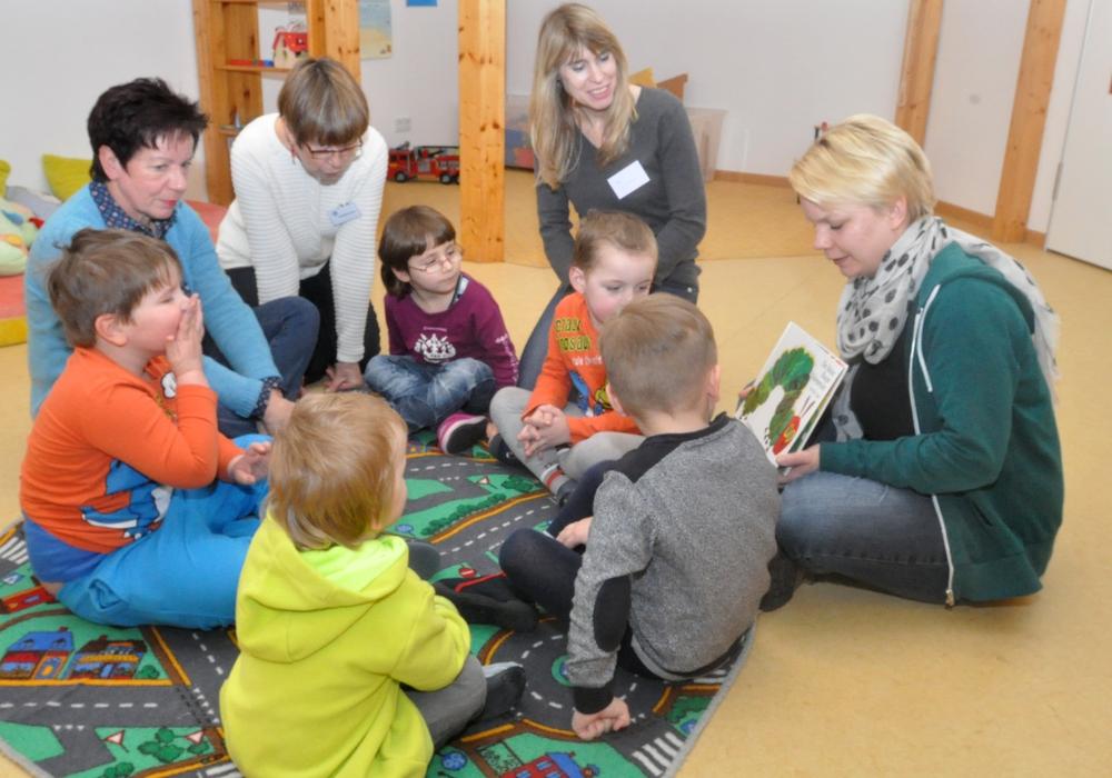Petra Winter (links) und Annette Scheunemann (Zweite von links) aus Uehrde hospitierten im Lebenshilfe-Kindergarten Siebenstein in der Schmetterlingsgruppe, wo die Erzieherin Wiebke Tolle (rechts) den Kindern ein Bilderbuch zeigt. Foto: Lebenshilfe