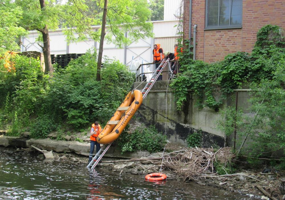 Das Schlauchboot wird am Hang eines offenen Gewässers zu Wasser gebracht. Foto: Feuerwehr