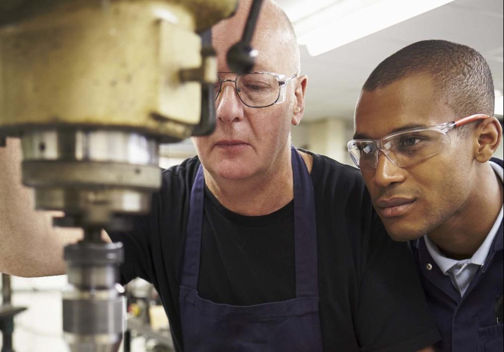 Ingenieur lehrt Azubi am Einsatz einer Fräsmaschine. Foto: Bundesagentur für Arbeit