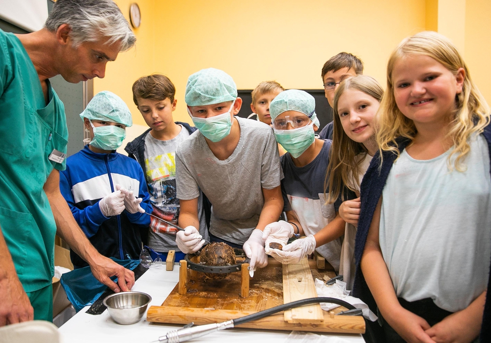 Operation an der Kokosnuss: Die Ärzte der Neurochirurgischen Klinik simulierten eine Kopfoperation, bei der die Kinder an einer Kokosnuss Original-Operationsinstrumente be- nutzen konnten. Foto: Klinikum Braunschweig / Jörg Scheibe
