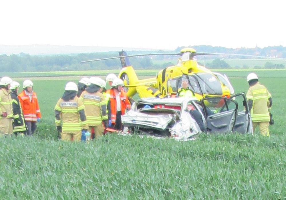 Der Rettungshubschrauber und die Feuerwehr am Unfallfahrzeug Foto: Polizei Wolfsburg