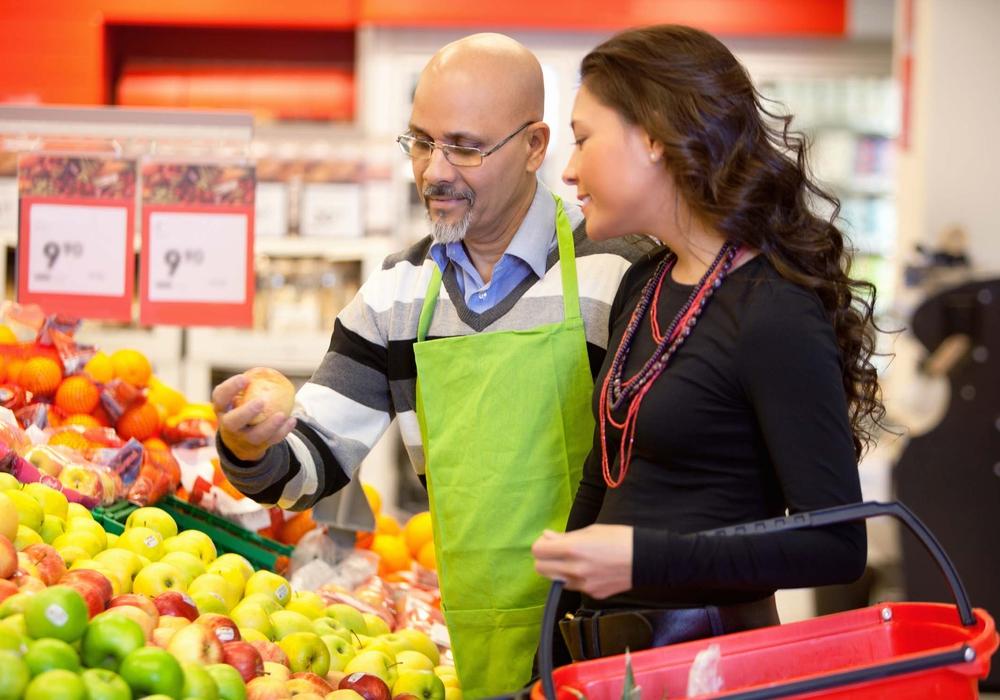 Ein Verkäufer in einem Supermarkt zeigt einer Kundin einen Apfel. Foto: Bundesagentur für Arbeit