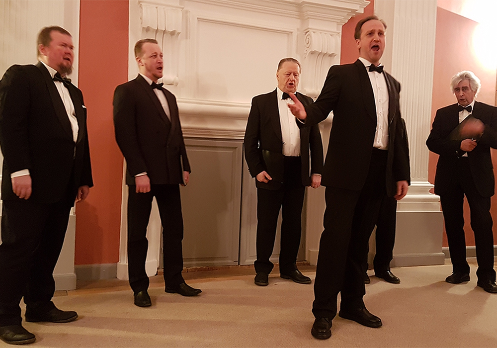 Das Vokalensemble Harmonie St. Petersburg trägt ein Stück mit Solisten vor. Rechts im Bold: Chorleiter Alexander Adrianov. Foto: Sickter Kulturinitiative