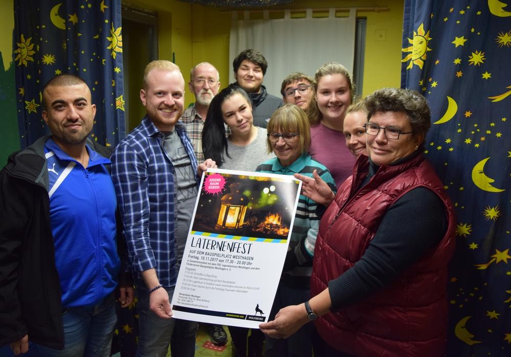 Mitarbeiter vom Bauspielplatz Westhagen sowie Ehrenamtliche desFördervereins präsentieren das Plakat zum diesjährigen Laternenumzug. Foto: Stadt Wolfsburg