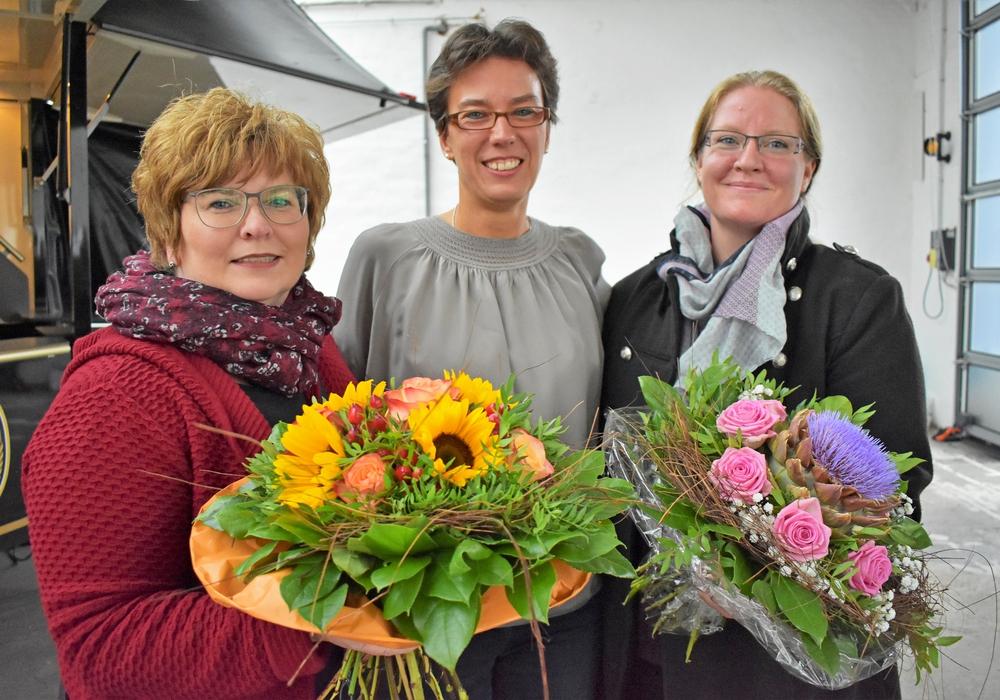 Die Dienststellenleiterin Samantha Brinkwirth (Mitte) überraschte ihre Mitarbeiterinnen Britta Goes (links) und Melanie Ebert mit einem schönen Blumenstrauß. Foto: Valea Schweiger/Johanniter