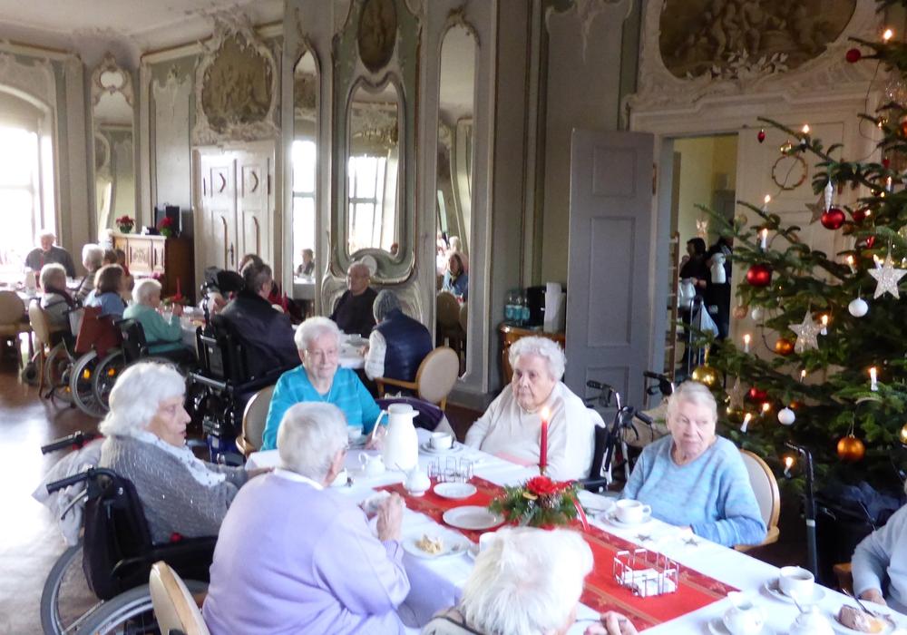 Die Vertreterinnen der Frauenhilfe mit den Bewohnern im adventlich geschmückten Spiegelsaal der Seniorenbetreuung Schloß Schliestedt. Foto: Seniorenbetreuung Schloß Schliestedt