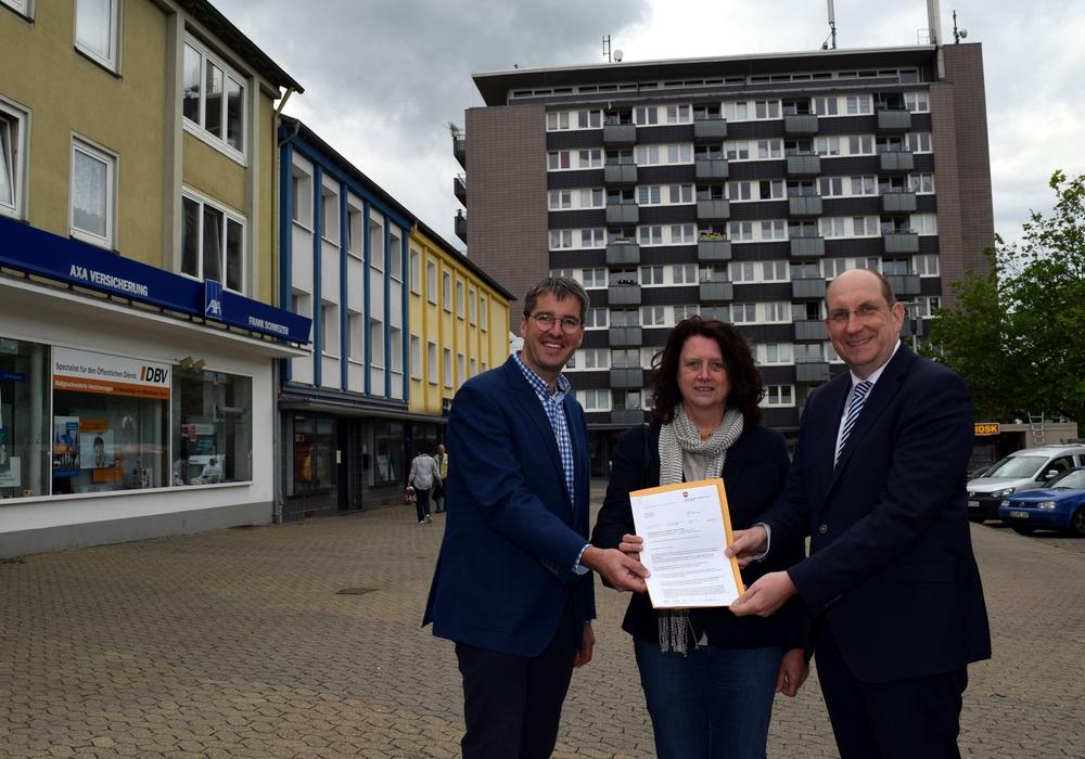 """Dr. Oliver Junk (links) und Marion Siegmeier nehmen auf dem Goslarer Marktplatz den Brief von Matthias Wunderling-Weilbier entgegen, der die Aufnahme in das Förderprogramm """"Soziale Stadt"""" verkündet. Foto: Stadt Goslar"""