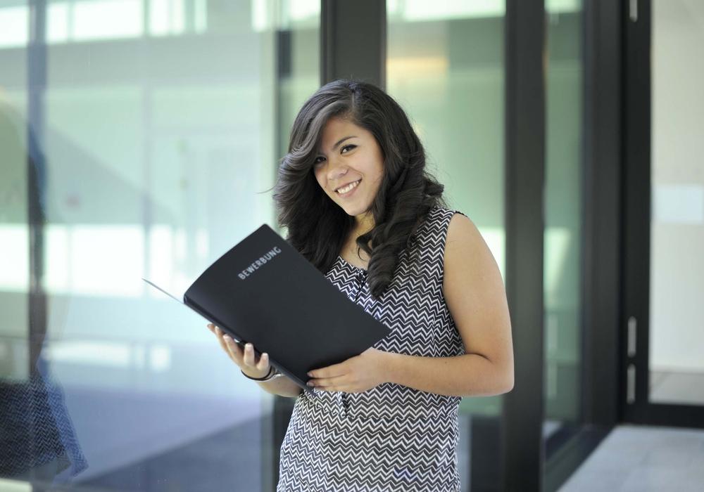 Diese Junge Frau hält eine Bewerbungsmappe in der Hand. Foto: Arbeitsgentur