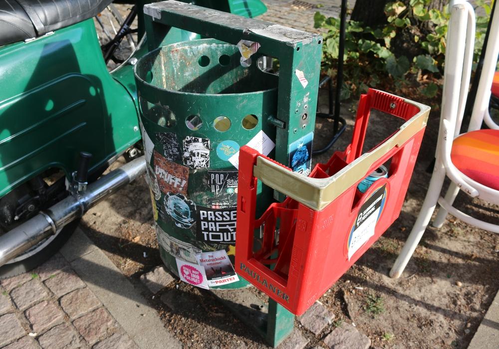 """Mit einer selbstgebauten Konstruktion am Mülleimer vor der """"Veränder.bar"""" wird dazu aufgefordert die Pfandflaschen daneben abzustellen. Foto: Werner Heise"""