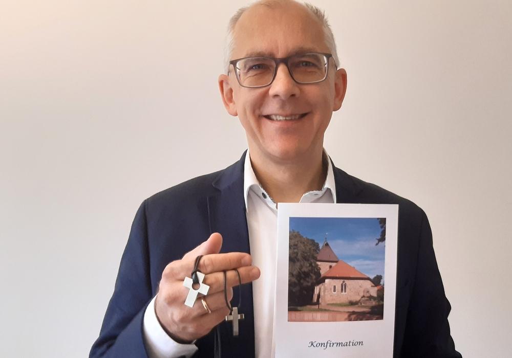 Superintendent Christian Berndt zeigt Konfirmationskreuze.