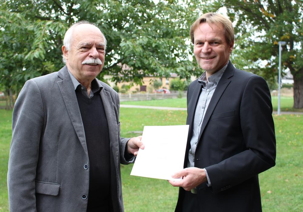 Der stellvertretende Bürgermeister Rolf Naue übergibt die Ernennungsurkunde zum Bürgermeister an seinen Sohn Jens Naue.